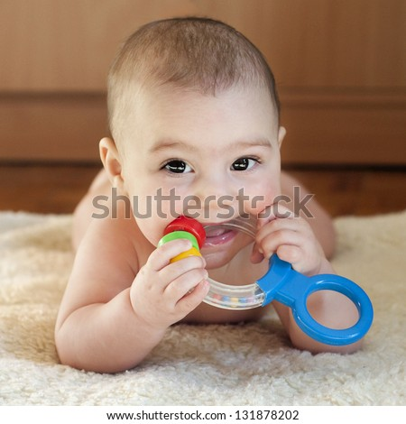 Portrait of a cute 6 month old baby, boy or girl, playing with a teething toy. - stock photo