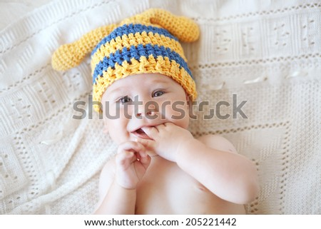 Portrait of a cute 4 months baby wearing crochet knit hat, top view point - stock photo