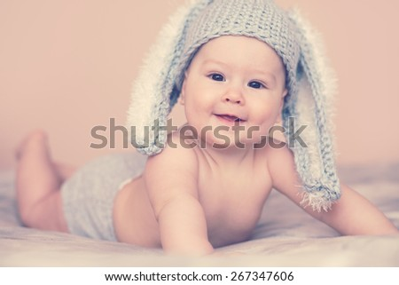 Portrait of a cute 6 months baby wearing rabbit hat - stock photo