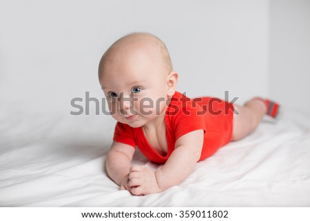 Portrait of a cute 5 months old baby boy in a red onesie lying down on a white blanket, holding hands together