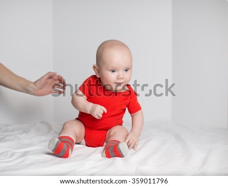 Portrait of a cute 5 months old baby boy in red onesie sitting down on a white blanket with mother's hand