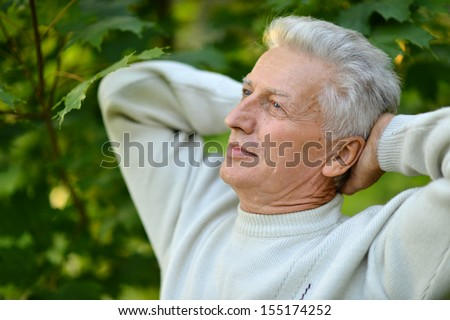 Portrait of a cute old thoughtful man at nature