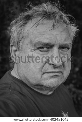 Portrait of a cute old thoughtful man in park - stock photo