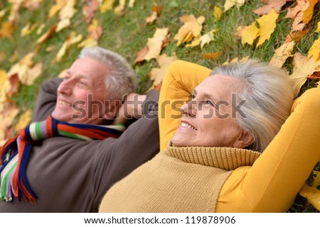 portrait of a cute older couple lying in autumn park - stock photo