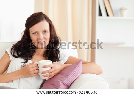 Portrait of a cute posing woman on a sofa in her living room