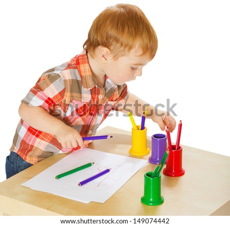 Portrait of a cute preschool boy drawing isolated on white background