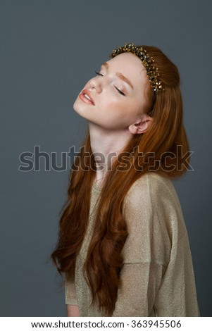 Portrait of a cute redhead woman with hoop on her head posing over gray background - stock photo