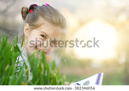 Portrait of a cute schoolgirl reading interesting book in natural environment