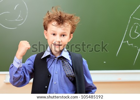 Portrait of a cute shaggy schoolboy in a classroom. - stock photo