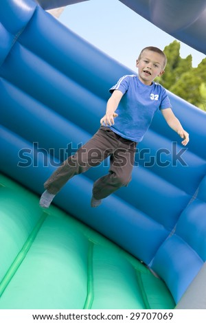 Portrait of a cute six year old boy jumping on a bouncy castle moonwalk