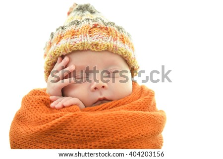 Portrait of a cute sleeping baby in orange plaid and hat over white background - stock photo