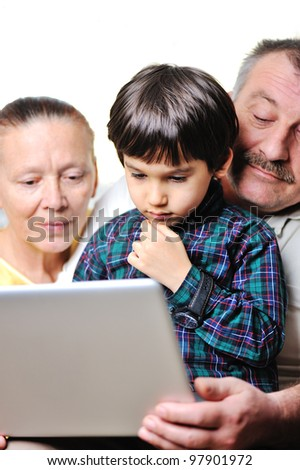 Portrait of a cute small boy using laptop with his grandparents