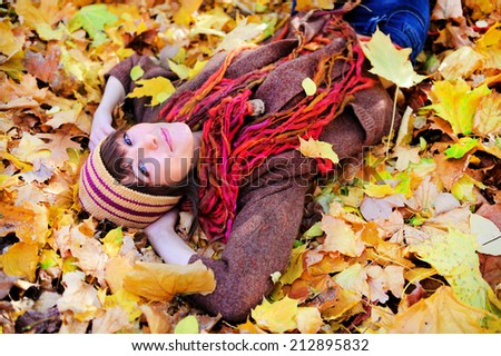 Portrait of a cute smiling woman looking at camera lying in autumn leaves in park, outdoor.  - stock photo