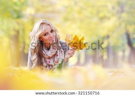 Portrait of a cute smiling woman lying in autumn leaves in park