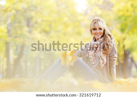 Portrait of a cute smiling woman sitting on autumn leaves in park - stock photo