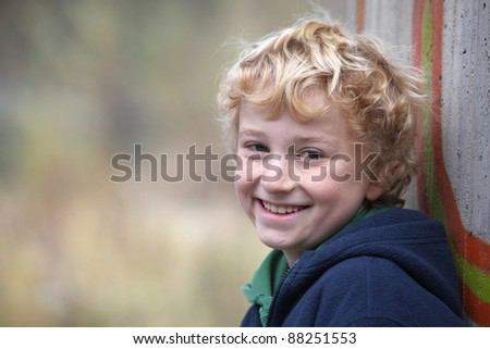 portrait of a cute smiling young boy leaning on a concrete wall - stock photo