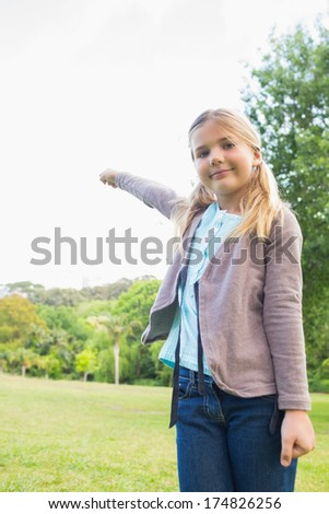 Portrait of a cute smiling young girl standing at the park - stock photo