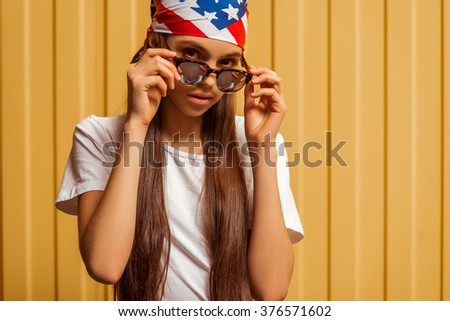 Portrait of a cute teenage girl in a bandana and sunglasses looking in camera and posing, standing against orange background - stock photo