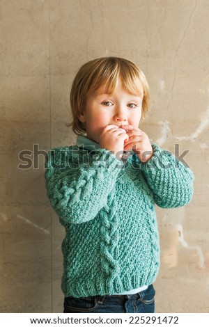 Portrait of a cute toddler boy, wearing green knitted pullover - stock photo