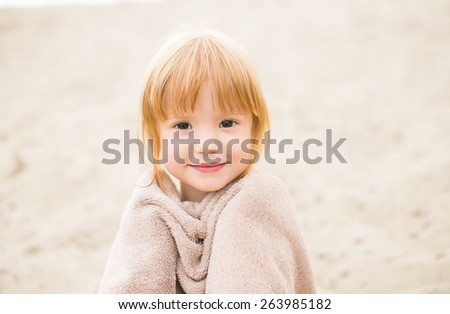 Portrait of a cute toddler girl with red hair wrapped in a towel at the beach smiling at camera. Little girl sitting on sand. Family time at the beach on hot summer day. - stock photo