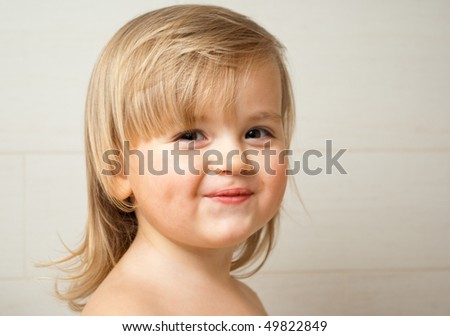 Portrait of a cute two-year-old girl smiling - stock photo