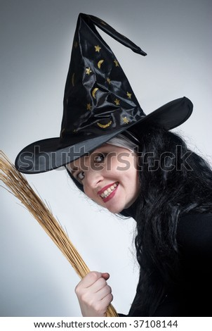 Portrait of a cute witch with hat playing with a broom