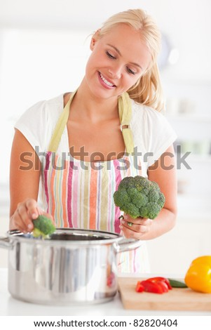 Portrait of a cute woman putting cabbage on water while wearing an apron - stock photo