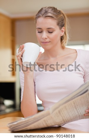 Portrait of a cute woman reading the news while having tea in her kitchen - stock photo