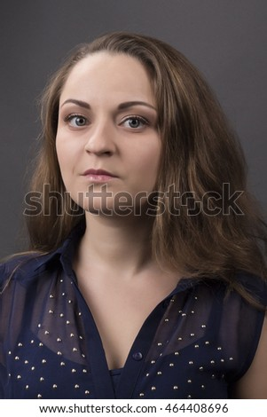 Portrait of a cute woman with a neat day make-up on a gray background