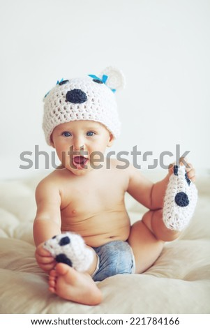 Portrait of a cute 1 year old baby dressed in a bear hat - stock photo
