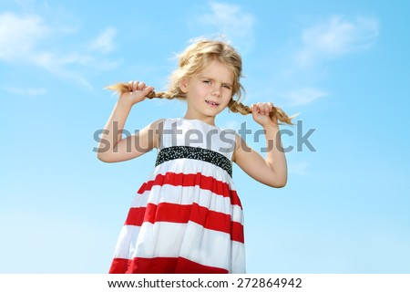 Portrait of a cute 5 year old girl on a blue sky background. Happy childhood.  - stock photo
