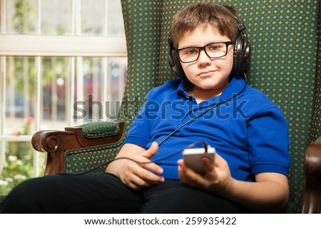 Portrait of a cute young boy wearing glasses and headphones and listening to music - stock photo