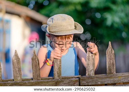 Portrait of a Cute Young Boy with Cowboy Hat Holding at the Wooden Fence, Smiling at the Camera - stock photo