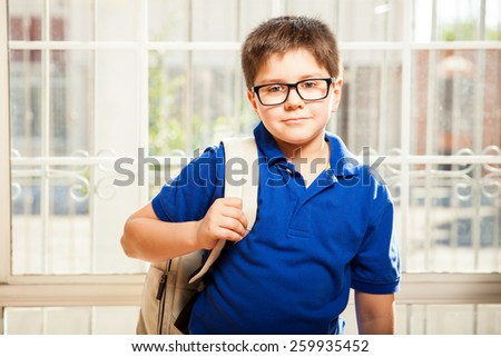 Portrait of a cute young boy with glasses carrying a backpack and standing ready for school - stock photo
