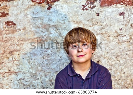 portrait of a cute young boy with old brick background