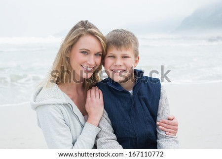 Portrait of a cute young boy with smiling mother at the beach - stock photo