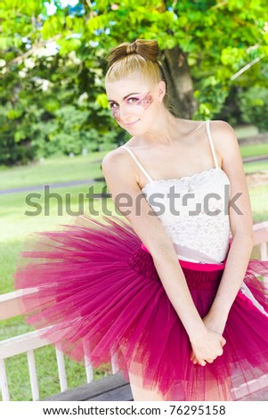 Portrait Of A Cute Young Dancing Ballerina Girl In Pink Dance Tutu And Glamorous Makeup Standing Outside At A Park Location In A Athletic Display Of Dancing - stock photo