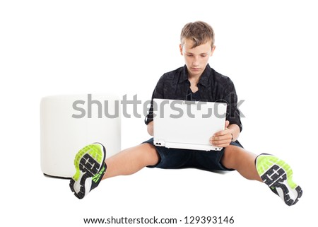 Portrait of a cute young European guy. A guy wearing a black shirt and shorts sitting on the floor in front of the laptop. Studio shot, isolated on white background. - stock photo