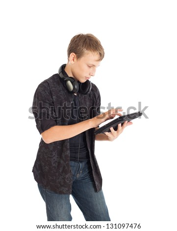Portrait of a cute young European guy wearing a black shirt and denim shorts. Boy holding a tablet. Studio shot, isolated on white background. - stock photo
