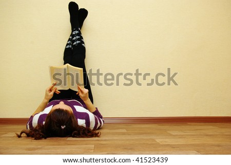 Portrait of a cute young female laying by the wall reading a book - stock photo