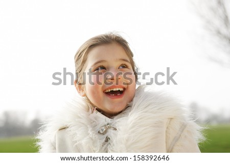 Portrait of a cute young girl child laughing and being joyful while in a green park during a sunny winter day, looking up to the sky and wearing a warm coat, outdoors. - stock photo