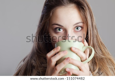 Portrait of a cute young lady in the winter with a cup of coffee.  - stock photo