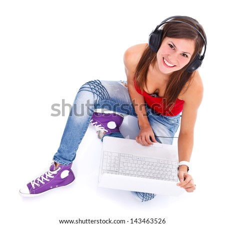 Portrait of a cute young smiling woman with headphones and notebook photographed from above. Studio shot.  - stock photo