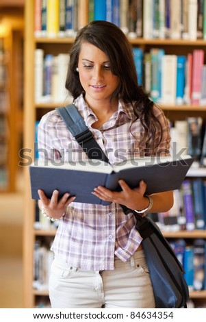 Portrait of a cute young student reading a book in the library - stock photo