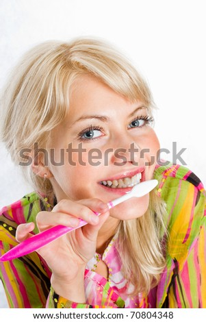 Portrait of a cute young woman cleaning her teeth - stock photo