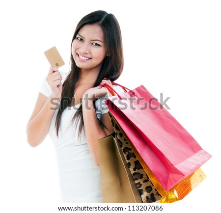 Portrait of a cute young woman holding credit card and shopping bags against white background.