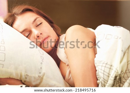 portrait of a cute young woman sleeping on the bed - stock photo