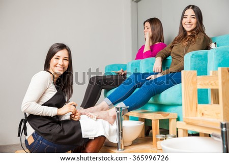 Portrait of a cute young woman working at a nail salon and giving a pedicure to a couple of women - stock photo