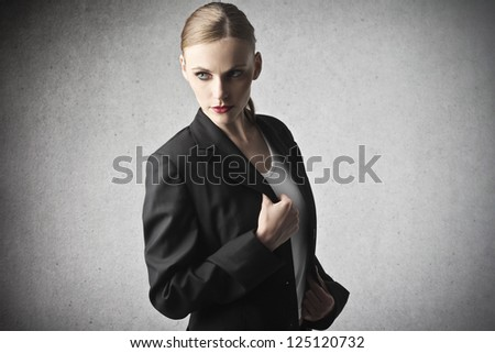 Portrait of a dark blonde woman with blue eyes in black jacket - stock photo