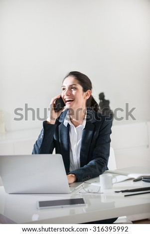 Portrait of a dark hair businesswoman sitting at a white desk in a luminous office She is wearing a black suit jacket, talking on the phone and working on her laptop, with her glasses next to her
